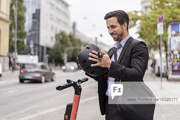 Businessman with e-scooter in the city putting on helmet