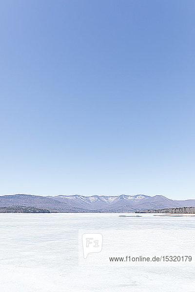 Idyllische Aufnahme von gefrorenem Eis auf dem Ashokan-Stausee vor strahlend blauem Himmel