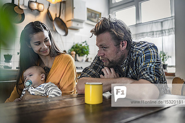 Family with baby sitting at kitchen table at home