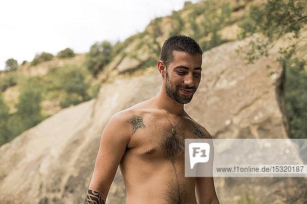 Porträt eines jungen Mannes mit Tätowierungen  nach unten blickend  Spanien