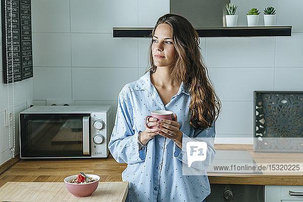 Porträt einer jungen Frau,  die zu Hause in der Küche einen Pyjama trägt und eine Tasse Kaffee hält