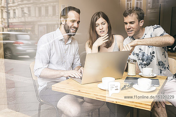 Group of friends sitting together in a cafe with laptop