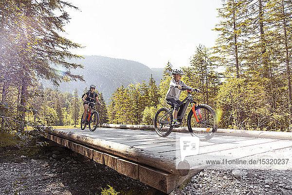 Mutter und Tochter fahren E-Mountainbike in den Bergen