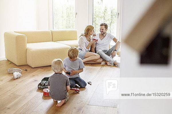 Glückliche Familie mit zwei Söhnen im Wohnzimmer ihres neuen Zuhauses