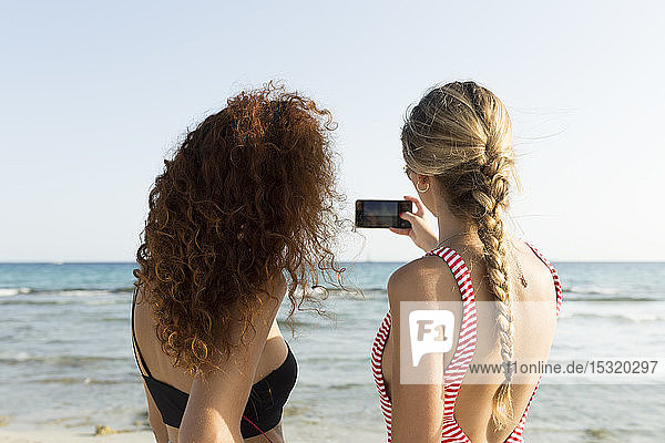 Best friends taking a selfie at the beach