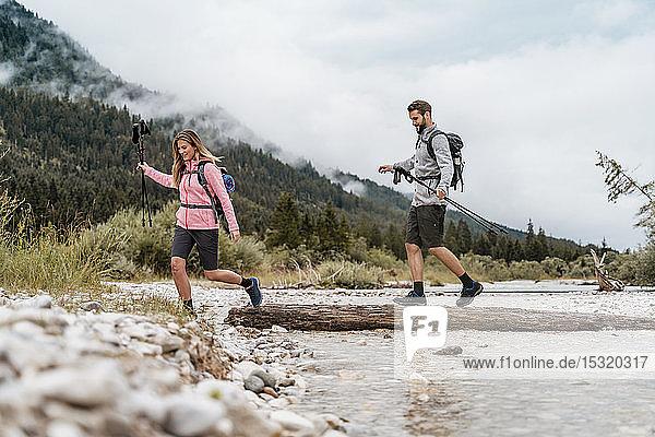 Junges Paar auf einer Wanderung über einen Fluss auf einem Baumstamm  Vorderriss  Bayern  Deutschland