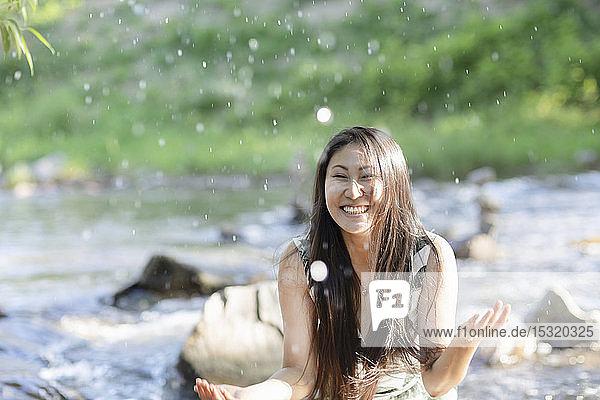 Junge Frau plätschert in einem Fluss