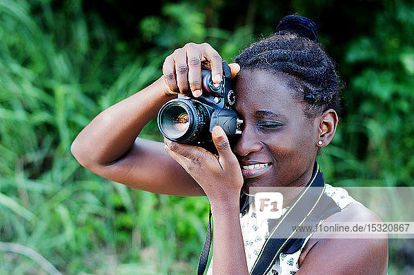 Travel  tourism and hobby. Young woman photographer taking pictures in the bush.