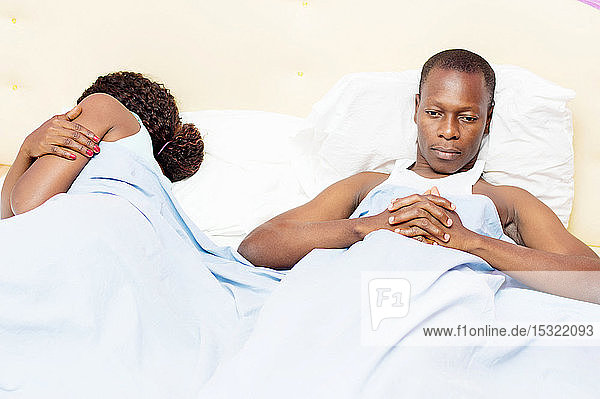 This young man lying in bed with his wife  is thoughtfully after a domestic dispute