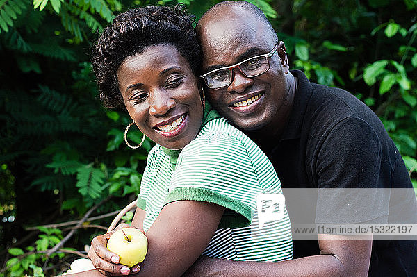 happy young couple hugging sitting in the bush picnic