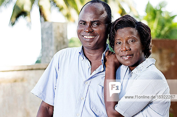 young young woman runs her husband by putting her hands on his shoulder.