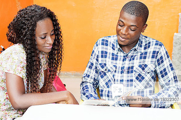 young couple sitting in a restaurant looking at the menu to oder food.