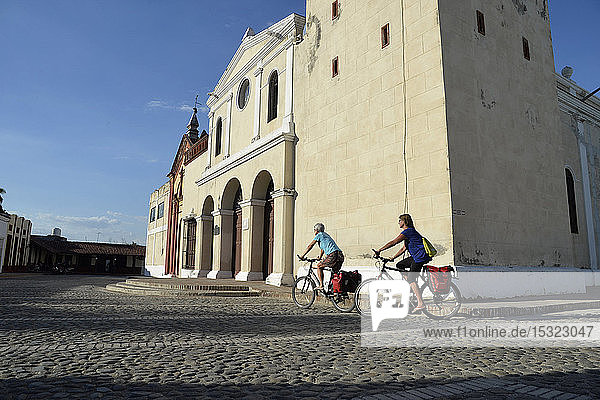 Cuba  eastern region  Bayamo  2 cyclo tourists are riding on a paved square in front of the San Salvador church