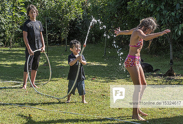 Two boys of 4 years old and 12 years old and a ten-year-old girl playing with a hose in the garden