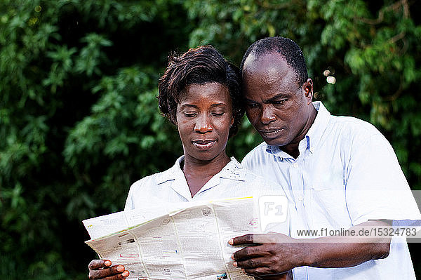 happy young couple traveling consult a regional map.