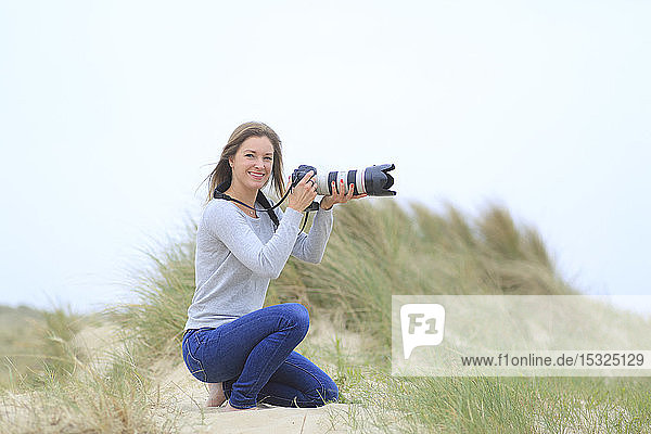Young woman taking pictures at the beach