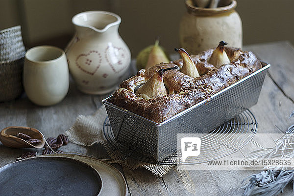 A loaf cake with pears in a baking tin