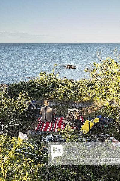Männer beim Picknick über dem Meer