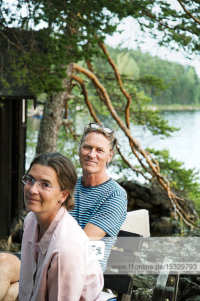 Mature couple relaxing by lake