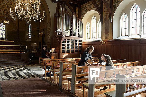 Priests talking on church pews