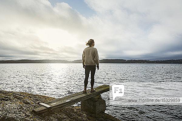 Junge Frau stehend neben dem See