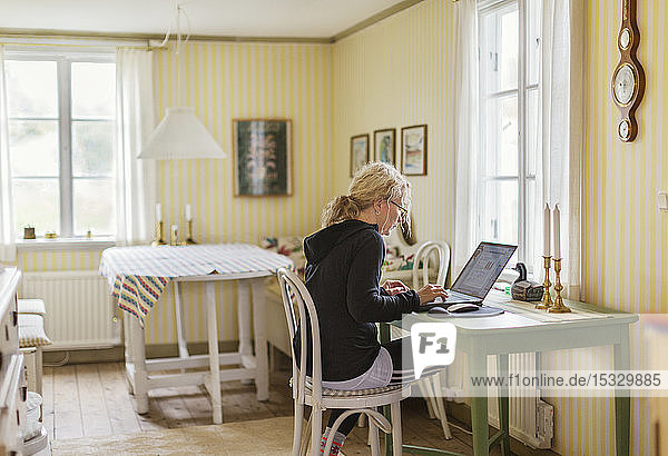 Mid adult woman on phone by laptop