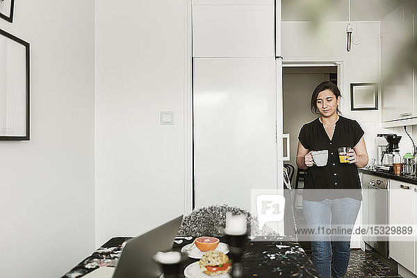Young woman carrying cups in kitchen