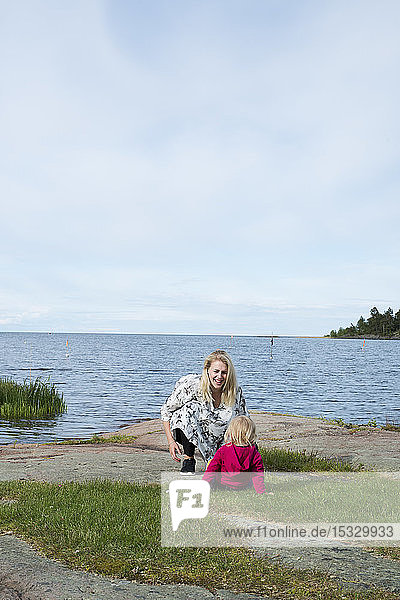 Young woman with daughter by lake