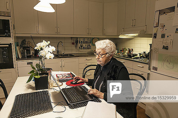 Senior woman using laptop in kitchen Senior woman using laptop in kitchen