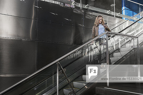 Young woman looking at cell phone on staircase Young woman looking at cell phone on staircase