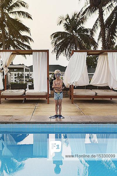 Boy standing poolside Boy standing poolside