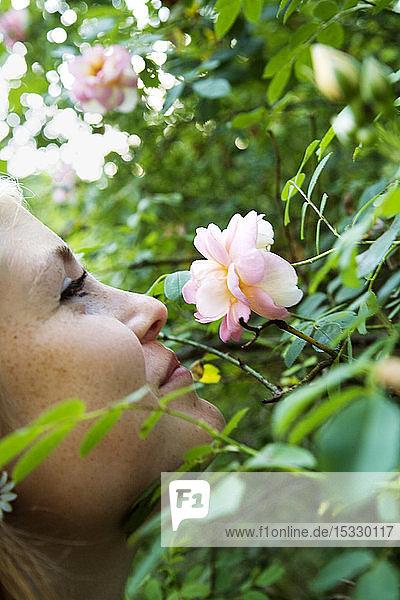 Teenager-Mädchen (16-17) riecht an Blumen