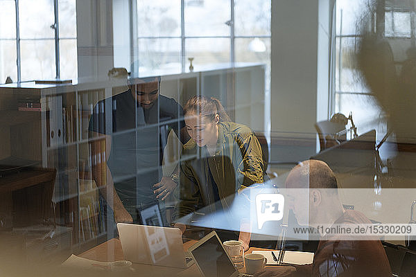 View through window of businesspeople in meeting