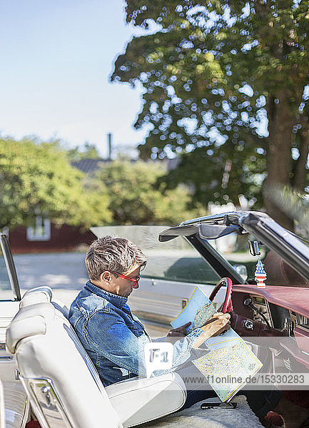 Mature woman reading map in vintage car