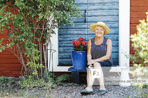 Senior woman sitting by flower pot in front of door Senior woman sitting by flower pot in front of door