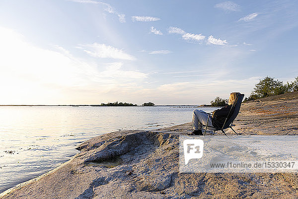 Woman sitting on chair next to sea