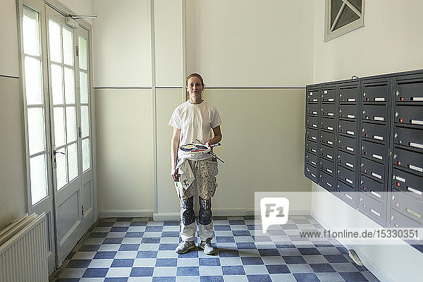 Painter by mailboxes in apartment building