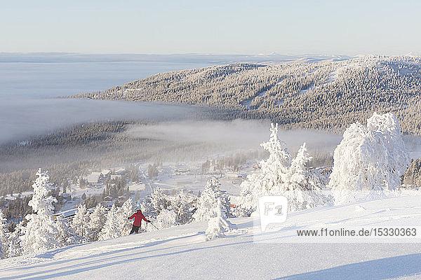 Person beim Skifahren an schneebedeckten Bäumen
