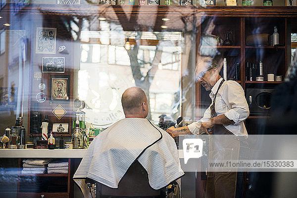 Friseur im Gespräch mit einem Kunden im Fenster des Friseursalons