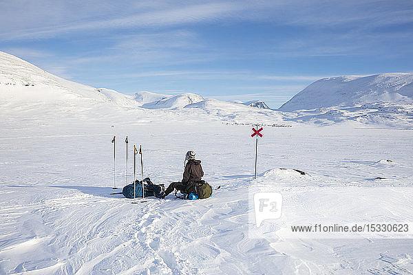 Woman resting on Kungsleden trail in Lapland  Sweden