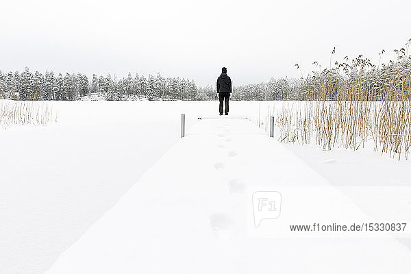Mature woman standing next to frozen lake in Ostergotland  Sweden Mature woman standing next to frozen lake in Ostergotland, Sweden