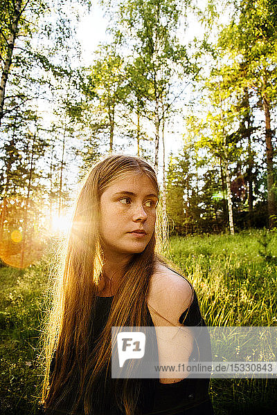 Portrait of young woman in forest at sunset