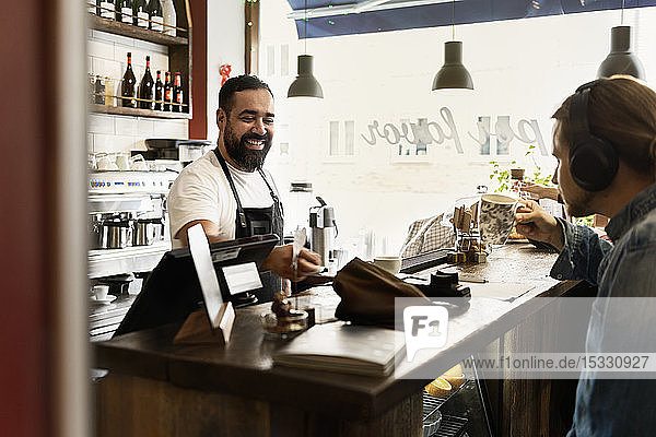 Smiling barista serving young man in cafe