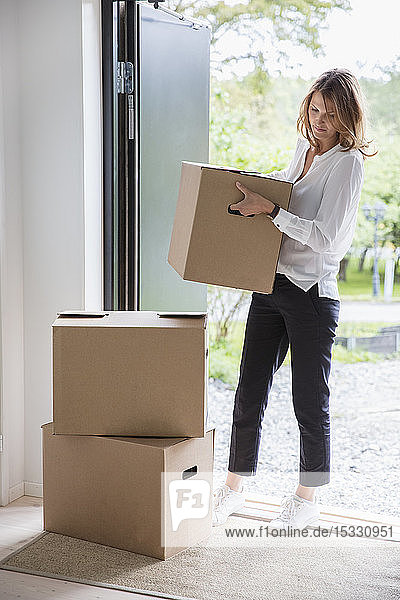 Woman carrying cardboard box into house
