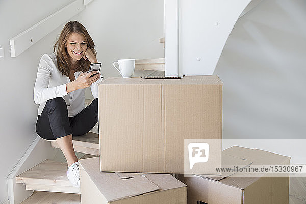 Woman sitting on staircase with smart phone and cardboard boxes