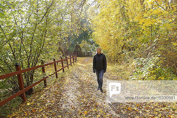 Ältere Frau geht im Wald spazieren