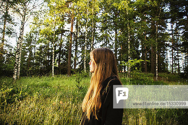 Young woman in forest at sunset