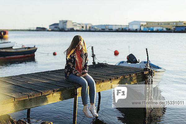 Woman sitting on jetty using smart phone Woman sitting on jetty using smart phone