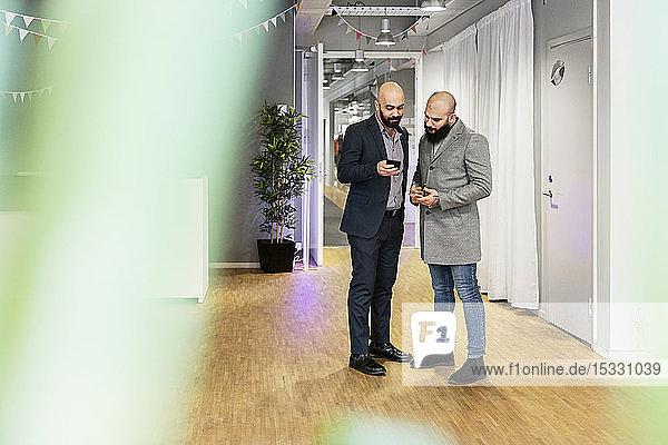 Männer schauen im Büro auf ihr Smartphone
