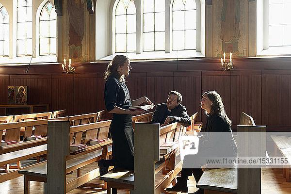 Priester sprechen auf Kirchenbänken